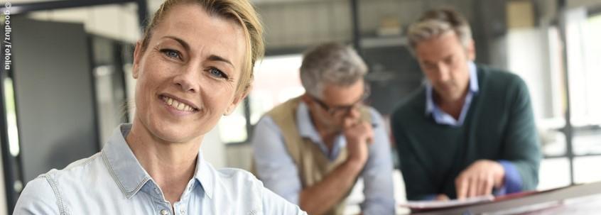 Eine Frau lächelt in die Kamera, im Hintergrund stehen zwei Männer an einem Tisch.